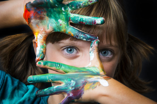 Little girl with watercolors on her hands.